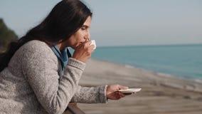 La mujer romántica sola está bebiendo el café por mañana en balcón con la opinión del mar almacen de video