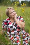 La mujer romántica del pensionista se relaja en hierba Fotos de archivo libres de regalías