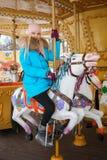 La mujer rubia adorable joven disfruta de las vacaciones de invierno en el carrusel del parque de la ciudad Concepto activo de la Fotos de archivo