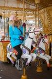 La mujer rubia adorable joven disfruta de las vacaciones de invierno en el carrusel del parque de la ciudad Concepto activo de la Imágenes de archivo libres de regalías