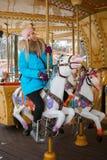 La mujer rubia adorable joven disfruta de las vacaciones de invierno en el carrusel del parque de la ciudad Concepto activo de la Imagen de archivo