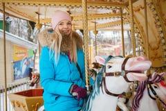 La mujer rubia adorable joven disfruta de las vacaciones de invierno en el carrusel del parque de la ciudad Concepto activo de la Foto de archivo