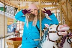 La mujer rubia adorable joven disfruta de las vacaciones de invierno en el carrusel del parque de la ciudad que hace gesto de v E Imagen de archivo