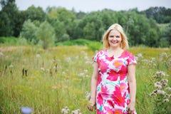 La mujer rubia adorable recorre en el prado imagen de archivo