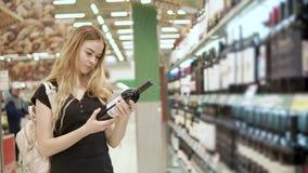 La mujer rubia adulta está leyendo las inscripciones en una botella de vino en un supermercado almacen de metraje de vídeo