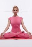 La mujer rubia atractiva atractiva hermosa que hace la yoga que se sienta en la posición de loto relaja y abre los chakras vestid Imagen de archivo libre de regalías