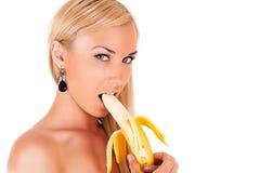 La mujer rubia atractiva come el plátano Foto de archivo
