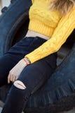 La mujer rubia atractiva hermosa que parece Jennifer Aniston miente en la rueda de goma grande de las ruinas imagen de archivo libre de regalías