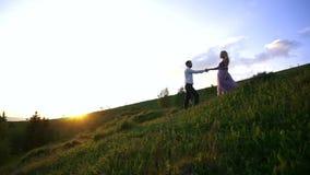 La mujer rubia atractiva joven en el vestido púrpura largo está dando la mano a su amante mientras que va abajo del prado ellos metrajes