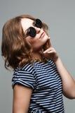 La mujer rubia atractiva joven que presentaba en la pared gris duplicó las gafas de sol Fotografía de archivo libre de regalías