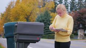 La mujer rubia atractiva toma el correo del buzón Campo en los E.E.U.U.