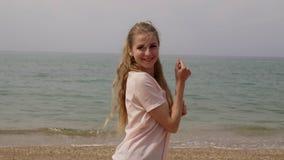 La mujer rubia baila y se ríe de la playa metrajes