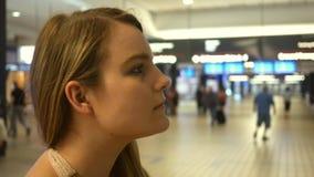 La mujer rubia bastante joven espera a un amigo para llegar el aeropuerto metrajes