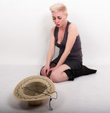 La mujer rubia borracha que se sienta en el piso, calcetines tirados abajo delante de ella es un sombrero Foto de archivo libre de regalías
