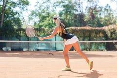 La mujer rubia caucásica joven está jugando al tenis al aire libre Visión desde la parte posterior Jugador de tenis en la acción  Foto de archivo