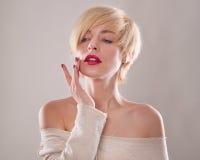 La mujer rubia con el pelo corto y una sonrisa hermosa con el dedo índice aislado Foto de archivo libre de regalías