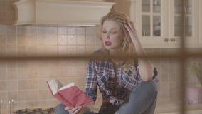La mujer rubia con estilo de pelo rubio largo se sienta encima de la tabla de cocina y de leer un libro Pasta, harina, rodillo almacen de video