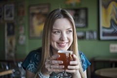 La mujer rubia con los ojos azules hermosos bebe un cubilete de cerveza Imagen de archivo