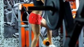 La mujer rubia con pantalones cortos rojos y ejercicios superiores del negro en el equipo del gimnasio almacen de metraje de vídeo