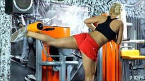 La mujer rubia con pantalones cortos rojos y ejercicios superiores del negro en el equipo del gimnasio almacen de video