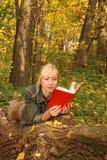 La mujer rubia con un libro está poniendo en el árbol Foto de archivo
