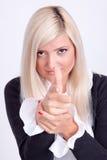 La mujer rubia da la fabricación de una muestra con el finger como el tiroteo Foto de archivo