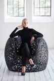 La mujer rubia de moda se sienta en una silla redonda Fotos de archivo libres de regalías
