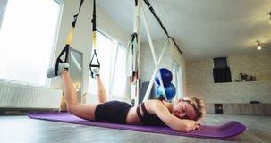 La mujer rubia deportiva en un estudio aerobio espacioso grande tiene un rato relajante que coloca en la estera del deporte despu metrajes