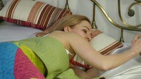 La mujer rubia despierta, mira el despertador y lo oculta debajo de la almohada 4K metrajes