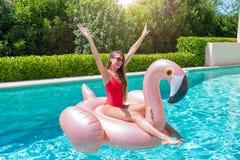 La mujer rubia disfruta de un día de verano caliente en la piscina con un flamenco flotable gigante fotos de archivo