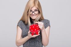 La mujer rubia emocionada joven puso un euro en la hucha Imágenes de archivo libres de regalías