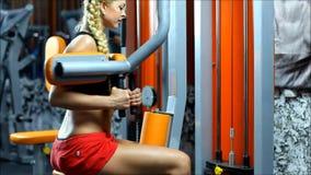 La mujer rubia en el gimnasio del equipo entrena a los obliques metrajes