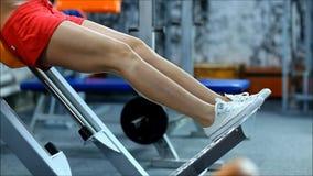 La mujer rubia en el gimnasio del equipo hace posiciones en cuclillas almacen de metraje de vídeo