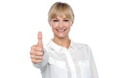 La mujer rubia en el traje formal que muestra los pulgares sube gesto Fotografía de archivo