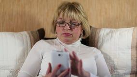 La mujer rubia en vidrios con el smartphone blanco se sienta en la cama almacen de video
