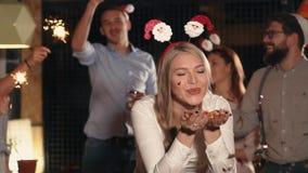 La mujer rubia encantadora está descargando confeti brillante brillante en la fiesta de Navidad almacen de metraje de vídeo