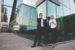 La mujer rubia está agujereando el teléfono móvil en manos, mientras que su jefe está hablando vía el teléfono móvil Imagen de archivo