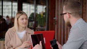 La mujer rubia está hablando con el hombre en terraza abierta en café y está mecanografiando en el ordenador portátil metrajes