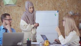 La mujer rubia está hablando en oficina, muchacha musulmán está haciendo la nota, hombre está escuchando almacen de video