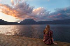 La mujer rubia está mirando puesta del sol en el lago Imágenes de archivo libres de regalías