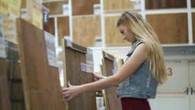 La mujer rubia está tocando un panel de madera grande para los revestimientos de suelos en una tienda almacen de video