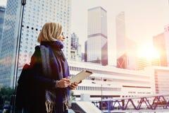 La mujer rubia está utilizando su almohadilla táctil portátil fotografía de archivo