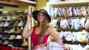 La mujer rubia feliz joven elige el sombrero de paja en tienda almacen de metraje de vídeo