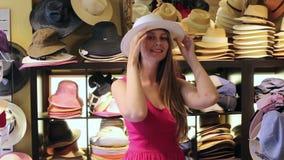 La mujer rubia feliz joven elige el sombrero de paja en tienda
