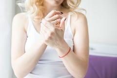 La mujer rubia hermosa aplica la crema para pelar y frota sus manos y hombro Cuidado de la piel y del cuerpo hidratando fotografía de archivo