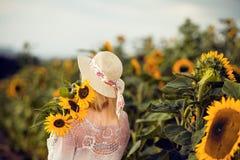 La mujer rubia hermosa con el pelo largo y el sunhat en los girasoles rurales colocan al aire libre imagenes de archivo