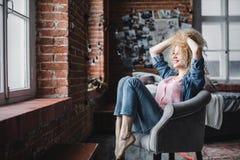 La mujer rubia hermosa con el pelo rizado se relaja en un desván o un hogar moderno foto de archivo
