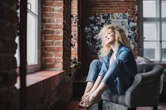 La mujer rubia hermosa con el pelo rizado se relaja en un desván o un hogar moderno foto de archivo libre de regalías
