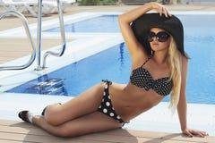 La mujer rubia hermosa en gafas de sol acerca a la piscina Verano Muchacha en bikini Mujer atractiva en sombrero Imagenes de archivo