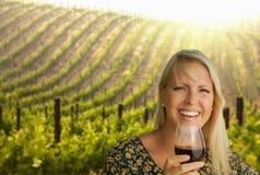 La mujer rubia hermosa goza del vidrio de vino en un viñedo foto de archivo libre de regalías